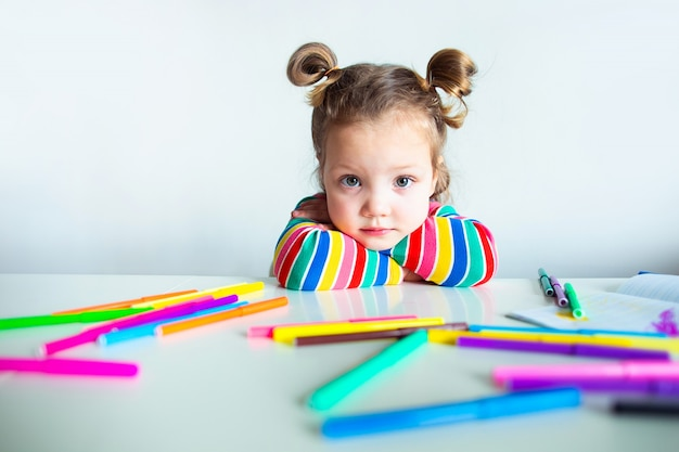 Little girl, a 3 year old girl, with a ponytail hairstyle in a multi-colored colorful striped jacket on a light wall at the table draws multicolored markers and smiles