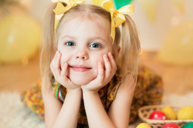 Little girl 3 years old lying on the floor with bright yellow clothes with easter eggs