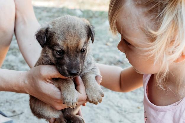 Маленькая девочка 3 года ласки щенка.