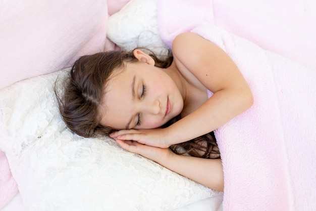 A little girl of 5-6 years old smiles in her sleep, the child lies in bed with her hands folded under her head