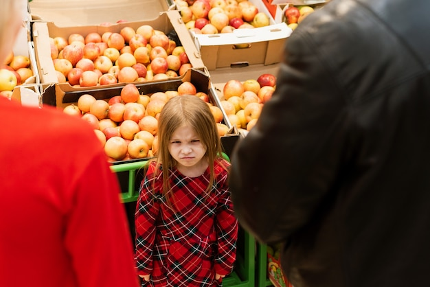 A little girl of 5 years old looks evil at mom and dad. upset hysterical girl with closed eyes crying loudly while manipulating parents and standing against food stall in supermarket