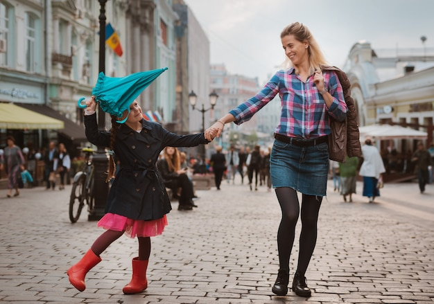 Little girl 6 years old child with an umbrella in rubber boots having fun with her mother on a bench in the center of moscow in the fall or spring.