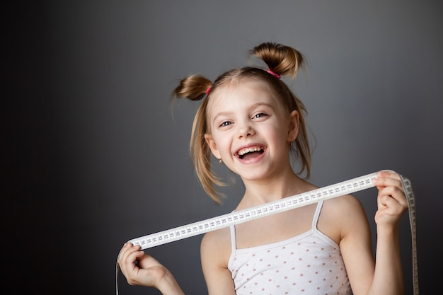 Little girl 7-8 years old laughing, child with a measuring tape (centimeter) on a gray wall