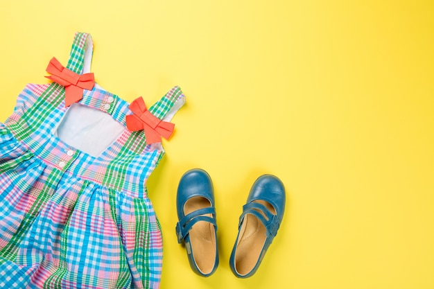 Little girl accessories. colorful dress and shoes on yellow surface.