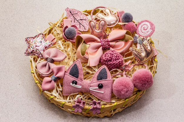 Little girl accessories lifestyle set. wicker basket, gray-pink color scheme. stone concrete background