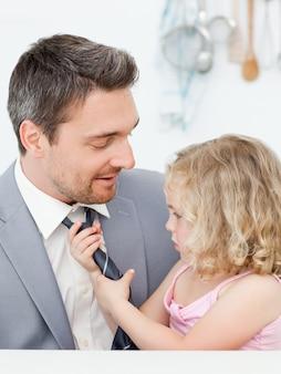 彼女の父親のネクタイを調整している少女