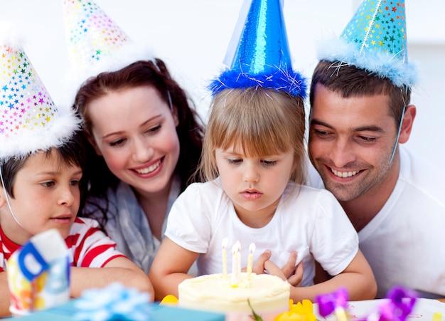 Маленькая девочка, любующаяся тортом в день своего рождения