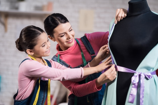 A little girl and an adult woman trying on clothes