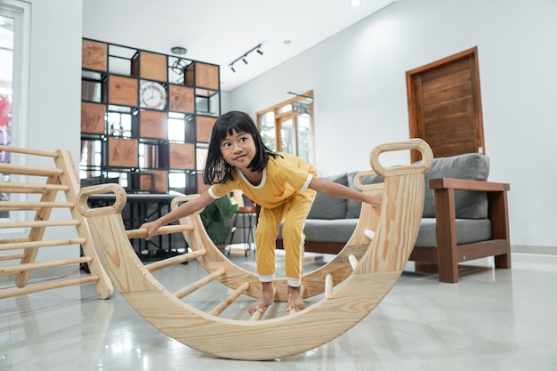 Little girl alone while playing balance in the pikler triangle toy in the living room