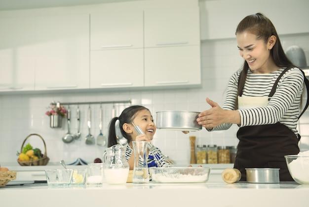 キッチンで生地をこねながら遊んで笑っているエプロンの少女とアジアのお母さん。自家製ペストリー。