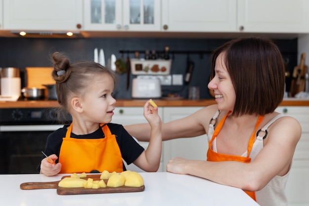 小さな女の子と美しいお母さんが家庭の台所で野菜を調理しています