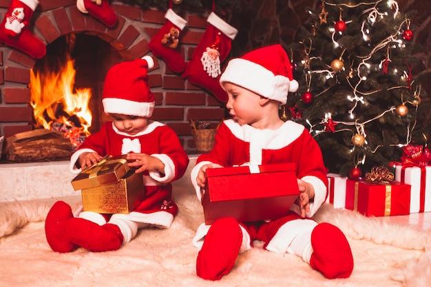 Маленькая девочка и мальчик сидят возле камина и елки с подарочными коробками. брат и сестра в костюмах санта-клауса