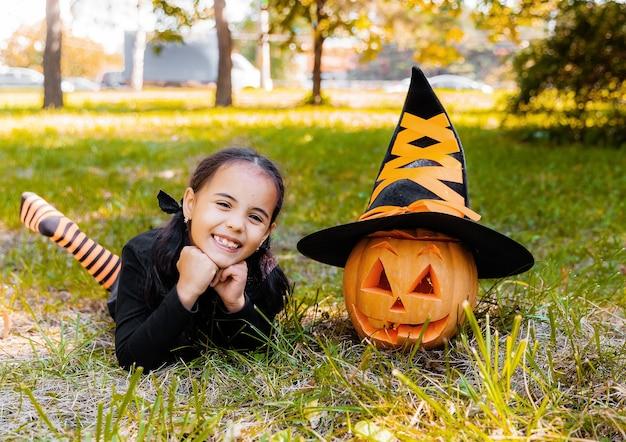 Маленькая девочка и мальчик, вырезая тыкву на хэллоуин. наряженные детские розыгрыши или угощения. дети угощают или угощают. ребенок в костюме ведьмы, играя в осеннем парке. малыш с фонарем из тыквы.