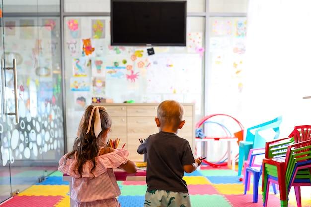 Маленькая девочка и мальчик, рисующий с цветной ручкой в бумаге на столе в игровой комнате, здоровом ребенке и концепции дошкольного образования.