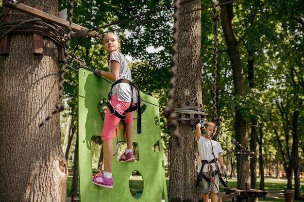 装備の小さな女の子と男の子がロープパークに登ります。吊橋に登る子供