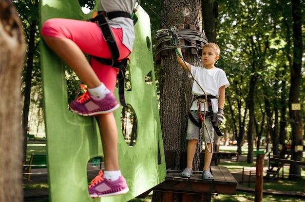 Маленькая девочка и мальчик в оборудовании поднимается в веревочном парке