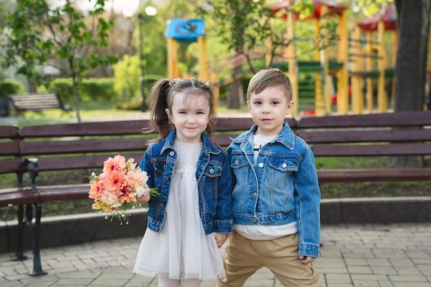 Маленькая девочка и мальчик в парке с букетом цветов.