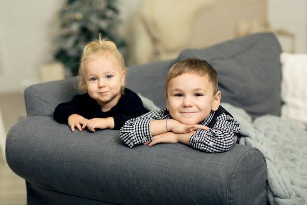 Маленькая девочка и мальчик, лежа на диване, покрытые серым вязаное одеяло и улыбается. брат и сестра морщатся и балуются новогодним декором и елкой.