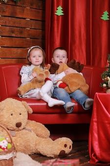 赤い色のクリスマススタジオのソファの上の小さな女の子と男の子。壁にクリスマスツリーとテディベア。