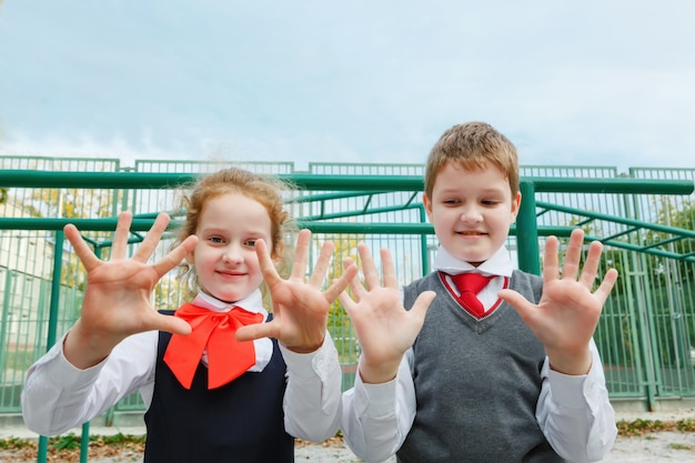 小さな女の子と男の子は5本の指を見せる。