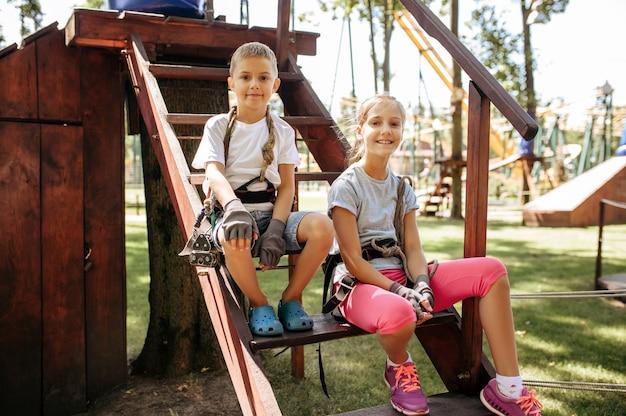 Маленькая девочка и мальчик, сидя на лестнице в веревочном парке