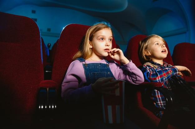 Маленькая девочка и мальчик смотрят фильм в кинотеатре
