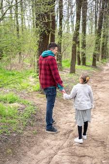 Маленькая девочка и папа гуляют в парке ранней весной в прохладную погоду.