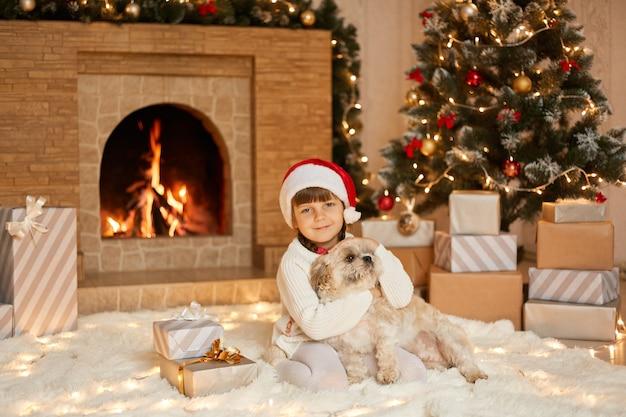 白い柔らかいカーペットの上に座っているクリスマスイブの少女と犬