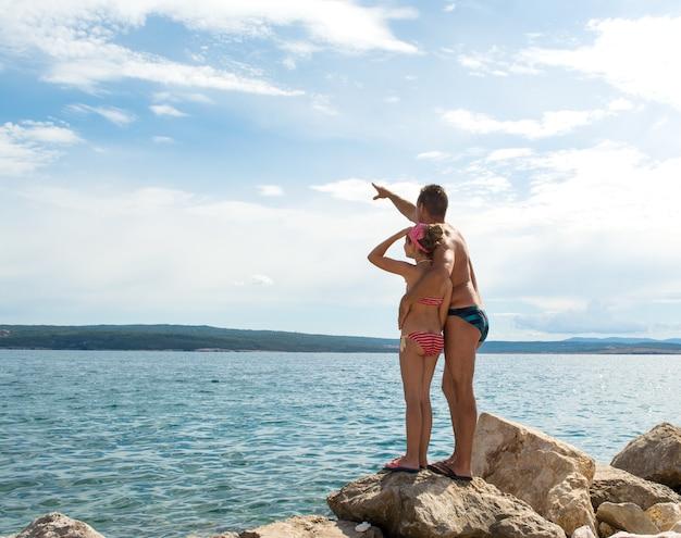 Маленькая девочка и отец, указывая вверх на пляже