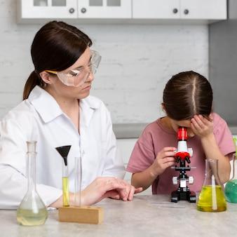 Маленькая девочка и учительница делают научные эксперименты с микроскопом