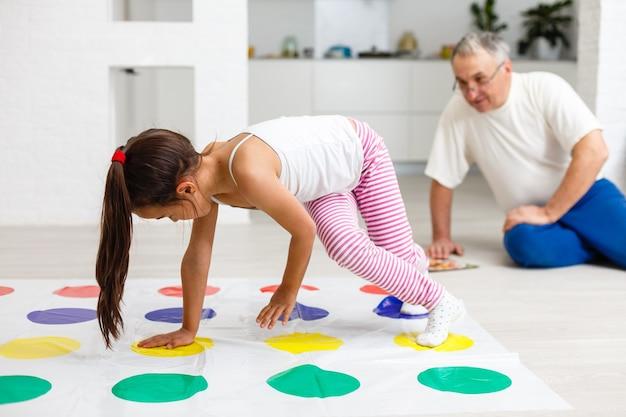 Маленькая девочка и дедушка играют в твистер дома
