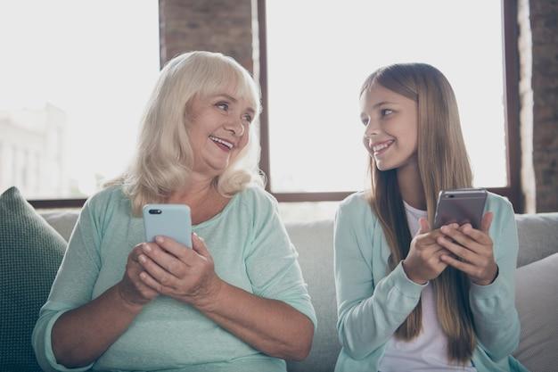 Маленькая девочка и бабушка, сидя на диване