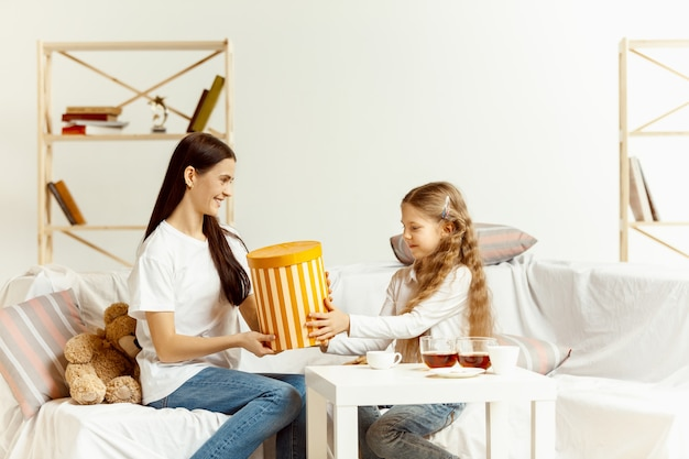 小さな女の子と彼女の魅力的な若い母親はギフトでソファーに座っていて、家で一緒に時間を過ごします。女性の世代。国際婦人デー。母の日おめでとう。