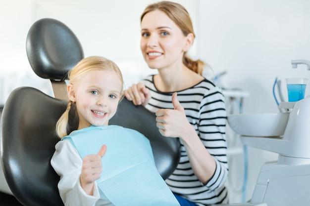 Маленькая девочка и ее любимая мама показывает палец вверх, пока девочка сидит в кресле стоматолога и ждет лечения