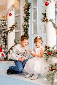 Маленькая девочка и ее брат открывают рождественские подарки. дети рассматривают снежный шар-сюрприз