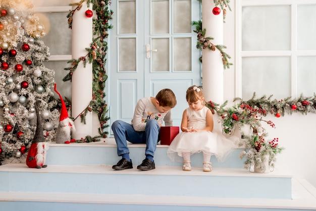 Маленькая девочка и ее брат открывают рождественские подарки. на ступеньках новогоднего домика