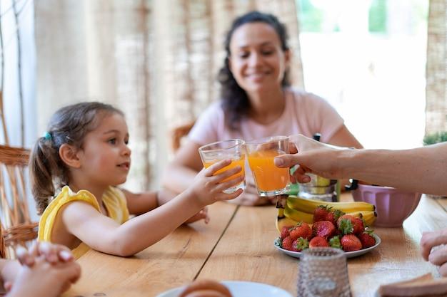 어린 소녀와 그녀의 아빠는 맛있는 과일 주스로 잔을 부딪치며 새로운 흥미로운 여름날을 기대하며 사랑하는 가족과 함께 아침 식사를 즐깁니다.