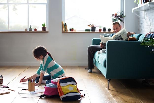 Маленькая девочка и ее отец занимаются своими делами в гостиной