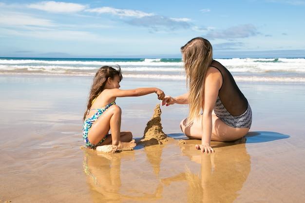 小さな女の子と彼女のお母さんはビーチで砂の城を建て、濡れた砂の上に座って、海での休暇を楽しんでいます