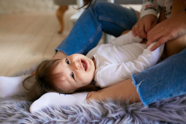 カジュアルなスタイルに身を包んだ小さな女の子と彼女のお母さんは床で遊んで楽しんで