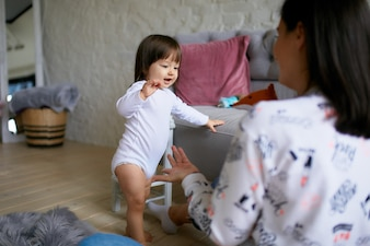 Little girl and her mom dressed in casual style have fun playing on the floor