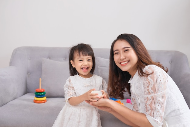 어린 소녀와 그녀의 엄마는 집에서 소파에 앉아 우유를 마시고 있습니다. 어머니와 보살핌, 건강한 식생활과 생활 방식, 초기 개발 개념, 복사 공간