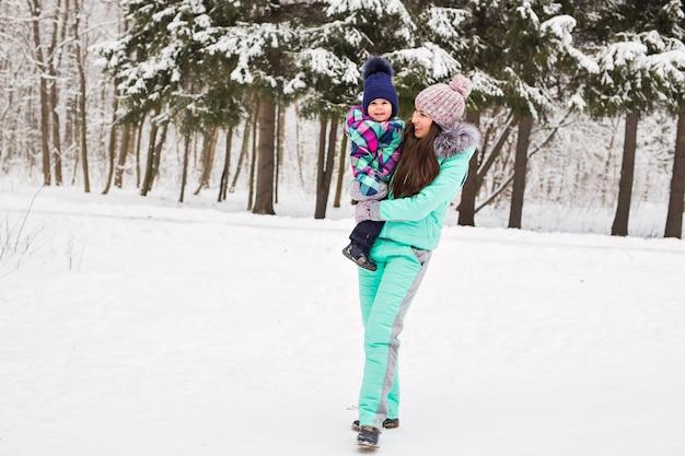 Маленькая девочка и ее мама веселятся в зимний день.