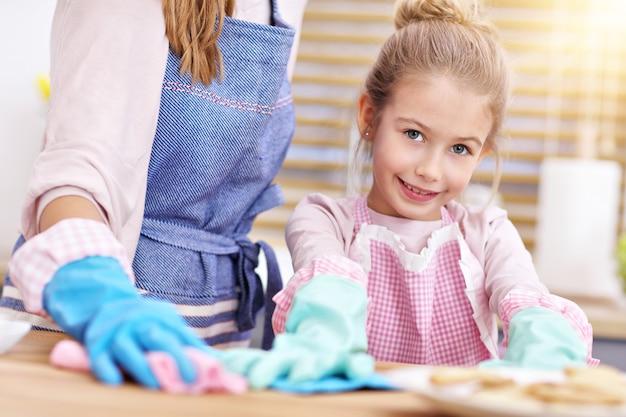 キッチンの掃除を楽しんでいるエプロンの少女と彼女のお母さん