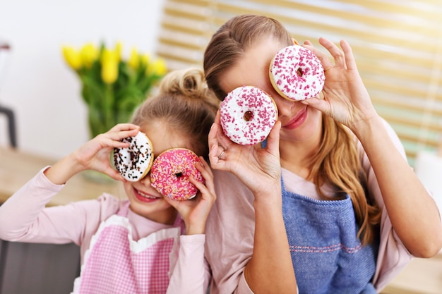 Маленькая девочка и ее мама в фартуках развлекаются на кухне