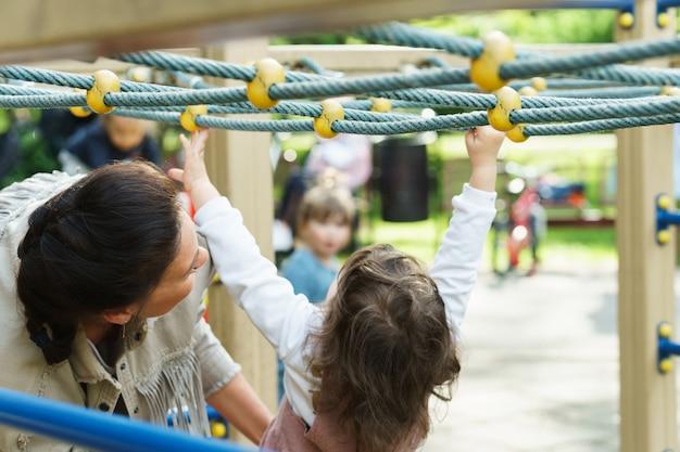 Маленькая девочка и ее мама играют на детской площадке в городском парке