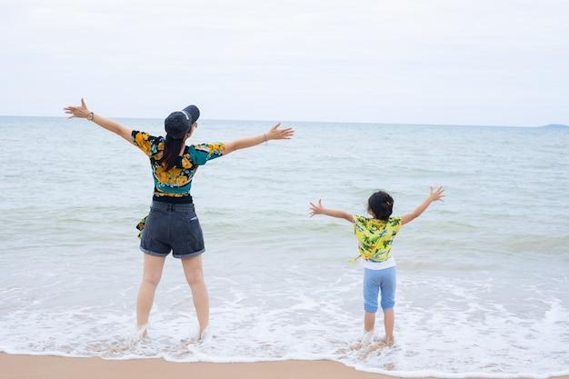 ビーチでの休暇中の少女と彼女の母親