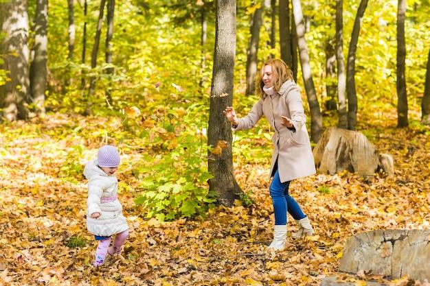 Маленькая девочка и ее мать играют в осеннем парке.