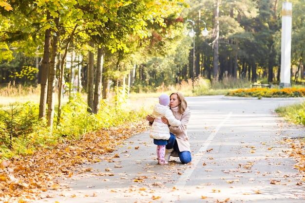 秋の公園で遊ぶ少女と母親