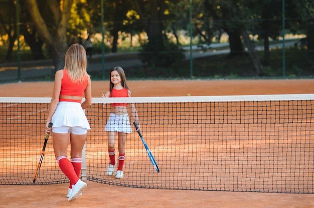 小さな女の子とコートでテニスをしている彼女の母親